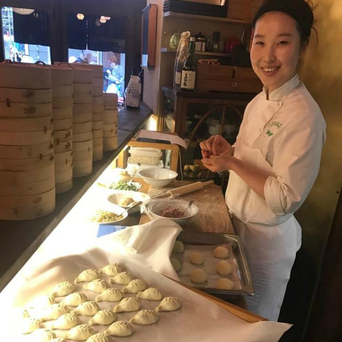 Cuoca asiatica mentre prepara i ravioli